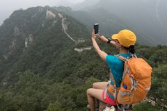 Woman hiker taking photo with smart phone on top of great wall royalty free stock images