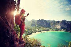 Woman hiker taking photo with smartphone at mountain cliff Stock Image