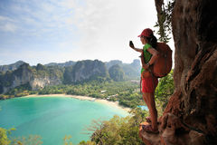 Woman hiker taking photo with smartphone at mountain cliff Stock Photo