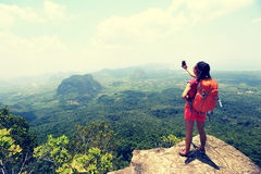 Woman hiker taking photo with smartphone on mountain peak cliff Stock Image