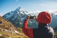 Woman hiker taking photo on the top of mountain Stock Image
