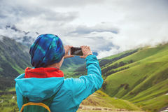 Woman hiker taking photo on the top of mountain Stock Photos