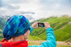 Woman hiker taking photo on the top of mountain Royalty Free Stock Images