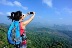 Woman hiker taking photos with cellphone at mountain peak Stock Photos