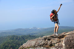 Woman hiker taking photos with cellphone at mountain peak Stock Images