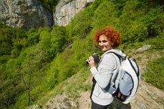 Woman hiker taking photos on a mountain trail Stock Photo