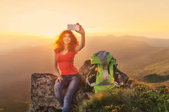 Woman hiker taking self photo on the mountain peak Royalty Free Stock Photo
