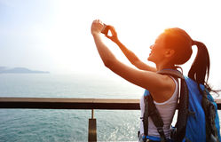 Woman hiker taking self photo seaside Stock Photos
