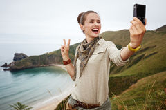 Woman hiker taking selfie with digital camera and showing victor Stock Photos