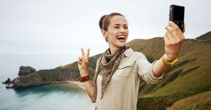 Woman hiker taking selfie with digital camera Royalty Free Stock Photography