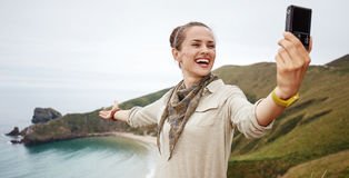 Woman hiker taking selfie in front of ocean view landscape Royalty Free Stock Photography