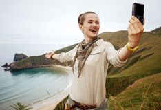 Woman hiker taking selfie in front of ocean view landscape Stock Images