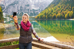 Woman hiker taking a selfie at Lake Bries with autumn colours Royalty Free Stock Images