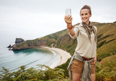 Woman hiker taking selfie with smartphone in front of ocean Royalty Free Stock Images