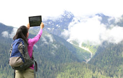 Woman hiker in tibet taking photo with digital tablet Royalty Free Stock Photos