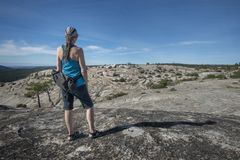 Woman hiker at top of rock mountain stock images