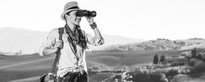 Woman hiker in Tuscany looking into distance through binoculars. Discovering magical views of Tuscany. healthy woman hiker in hat with bag on Tuscany hike Royalty Free Stock Photography