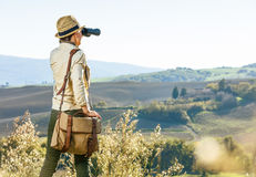 Woman hiker in Tuscany looking into distance through binoculars. Discovering magical views of Tuscany. Seen from behind woman hiker with bag enjoying Tuscany Royalty Free Stock Photo