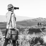 Woman hiker in Tuscany looking into distance through binoculars. Discovering magical views of Tuscany. Seen from behind woman hiker with bag enjoying Tuscany Royalty Free Stock Image