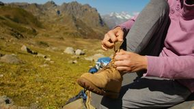 Woman Hiker tying boot laces on rock, high in the mountains stock footage