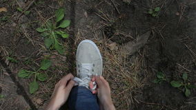 Woman hiker tying laces on sneakers at forest trail, close up, POV. Girl hiker tying laces on sneakers at forest trail, close up, POV stock footage