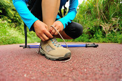 Woman hiker tying shoelace on forest trail Stock Photography