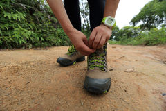 Woman hiker tying shoelace on forest trail Royalty Free Stock Photos