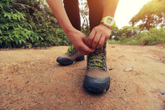 Woman hiker tying shoelace on forest trail Stock Photo