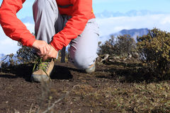 Woman hiker tying shoelace of hiking boots on mountain peak Royalty Free Stock Images
