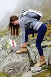 Woman hiker tying the shoelaces Stock Photo
