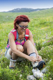 Woman hiker tying the shoelaces in mountains Royalty Free Stock Photo
