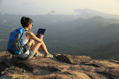 Woman hiker use digital tablet at mountain peak Stock Photography