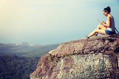 Woman hiker use digital tablet at mountain peak Stock Images