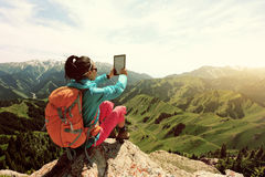 Woman hiker use digital tablet taking photo on mountain peak cliff Royalty Free Stock Image