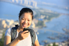Woman hiker use smart phone at mountain peak Royalty Free Stock Image