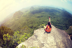 Woman hiker use smartphone taking photo on seaside mountain top Stock Photography