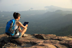 Woman hiker use tablet mountain peak Royalty Free Stock Photography