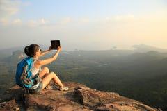 Woman hiker use tablet mountain peak Royalty Free Stock Image