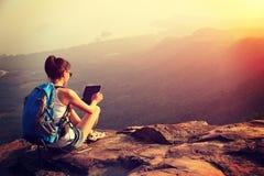 Woman hiker use tablet mountain peak Stock Photo