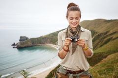 Woman hiker viewing photos in front of ocean view landscape Stock Photography