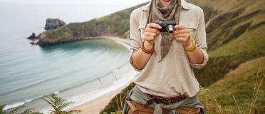Woman hiker viewing photos in front of ocean view landscape Royalty Free Stock Image