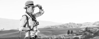 Woman hiker with vintage photo camera looking into the distance. Discovering magical views of Tuscany. young woman hiker in hat with bag hiking in Tuscany with Stock Photo
