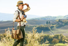 Woman hiker with vintage photo camera looking into the distance. Discovering magical views of Tuscany. young woman hiker in hat with bag hiking in Tuscany with Royalty Free Stock Images