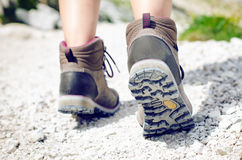 Woman hiker walk on a rocky ground. Sunny day.Trekking boots.Lens flare. Succesful backpacker. Stone. Step Royalty Free Stock Photography