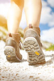 Woman hiker walk on a rocky ground. Sunny day.Trekking boots.Lens flare. Succesful backpacker. Stone. Step Stock Images