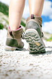 Woman hiker walk on a rocky ground. Sunny day.Trekking boots.Lens flare. Succesful backpacker. Stone. Step Stock Photos
