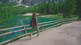 Woman hiker walking along the road near Lago di Braies stock video