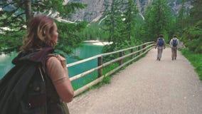 Woman hiker walking along the road near Lago di Braies stock video footage