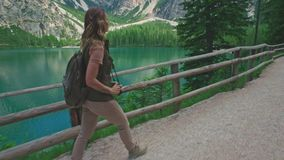 Woman hiker walking along the road near Lago di Braies stock footage