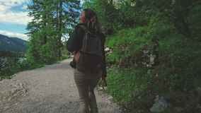 Woman hiker walking around the Braies lake and enjoys his spectacular sceneries, Dolomites, Italy. Alps stock footage